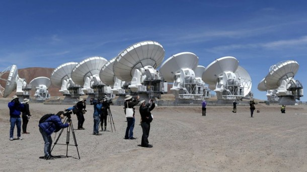 Members of the media work in front of the parabolic antennas of the ALMA project at the El Llano de Chajnantor in the Atacama desert