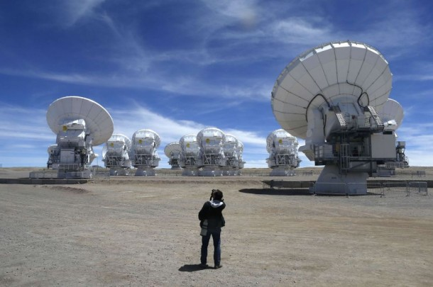 A member of the media takes pictures of the parabolic antennas of the ALMA project at the El Llano de Chajnantor in the Atacama desert