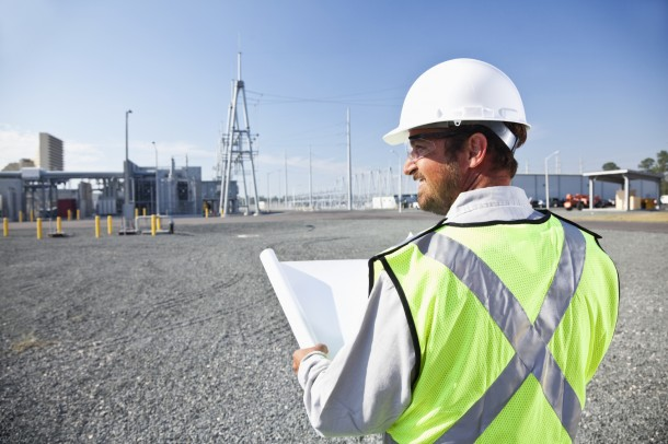 Engineer holding plans surveying power station