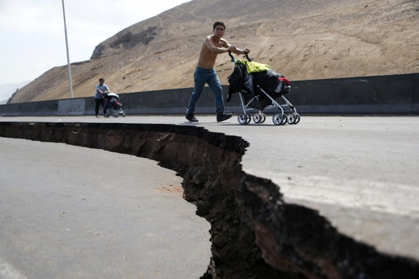 Residents push prams along a damaged road leading to Alto Hospicio commune after a series of aftershocks in Iquique