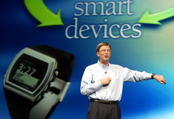 BILL GATES SHOWS THE NEW FOSSIL SPOT WATCH AT COMEX.