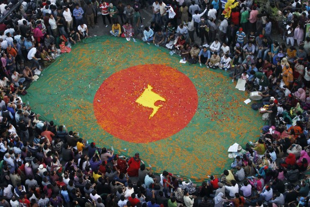 People observe a sit-in protest around a national flag of Bangladesh with a map of the country on it, made by flowers, as they attend a mass demonstration at Shahbagh intersection, demanding capital punishment for Bangladesh's Jamaat-e-Islami senior leader Abdul Quader Mollah, after a war crimes tribunal sentenced him to life imprisonment, in Dhaka February 9, 2013. Thousands of protesters rallied in cities across Bangladesh to demand the execution of an Islamist leader sentenced to life in prison for war crimes committed during the 1971 independence conflict. Picture taken February 9, 2013.  REUTERS/Andrew Biraj (BANGLADESH - Tags: TPX IMAGES OF THE DAY POLITICS CIVIL UNREST)