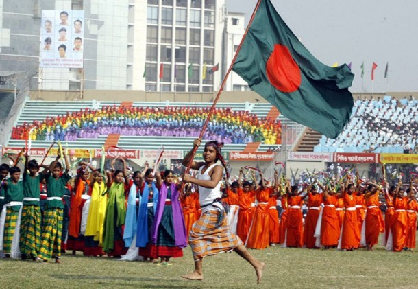 A school boy runs with a Bangladeshi flag during a performance to celebrate the 36th anniversary of Victory Day in Dhaka stadium December 16, 2007. Bangladesh won independence from Pakistan on this day following a nine month war in 1971. REUTERS/Rafiqur Rahman (BANGLADESH)
