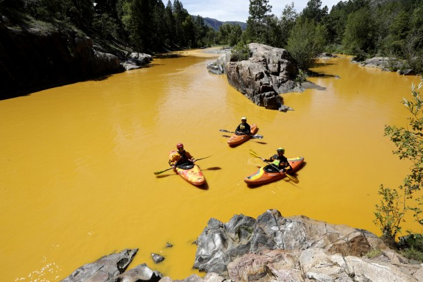 Aug. 6, 2015 - Durango, USA - People kayak in the Animas River near Durango, Colo., Thursday, Aug. 6, 2015, in water colored from a mine waste spill. The U.S. Environmental Protection Agency said that a cleanup team was working with heavy equipment Wednesday to secure an entrance to the Gold King Mine. Workers instead released an estimated 1 million gallons of mine waste into Cement Creek, which flows into the Animas River. (Jerry McBride/The Durango Herald via AP) MANDATORY CREDIT (Credit Image: © Jerry Mcbride/PA Wire via ZUMA Press)