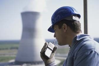 Side profile of a worker talking on a walkie-talkie at a power plant