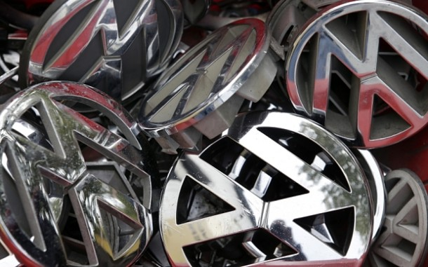 FILE - In this Sept. 23, 2015 file photo, company logos of the German car manufacturer Volkswagen sit in a box at a scrap yard in Berlin, Germany. Who knew about the deception, when did they know it and who directed it? Those are among questions that state and federal investigators want answered as they plunge into the emissions scandal at Volkswagen that has cost the chief executive his job, caused stock prices to plummet and could result in billions of dollars in fines. Legal experts say the German automaker is likely to face significant legal problems, including potential criminal charges.  (AP Photo/Michael Sohn, File)