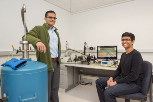 Berkeley Lab faculty scientist and UC Berkeley professor Ali Javey (left) and graduate student Sujay Desai created the smallest transistor to date. Next to them is a vacuum probe station used to measure the electrical characteristics of the 1-nanometer-long transistors. (Credit: Marilyn Chung/Berkeley Lab)