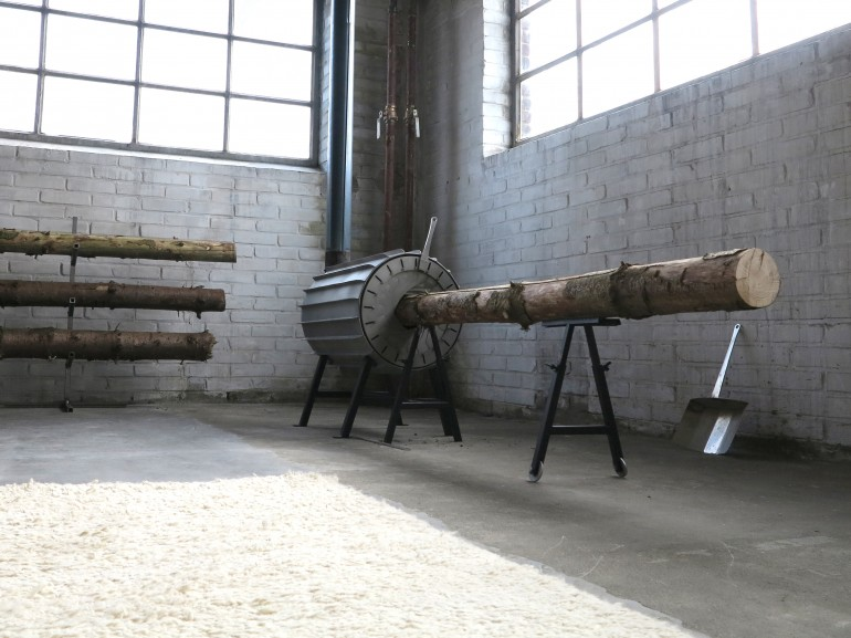 Users start by placing a log on the adjustable-height support stand, then pushing it into ...
