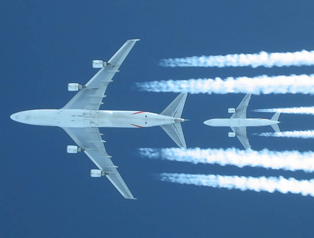 shot of this EK/Atlas Air 747 (2000ft above us) being chased by EK B777-200 (A6-EML, 4000ft above us) right at its tail. Captured out of a EK (now thats coincidence...) B777 flightdeck (through left #1 window upwards - thats why the neck was twisted ;-). Us at FL340, 747 at 360, other B777 at 380. Canon S50 max zoom.